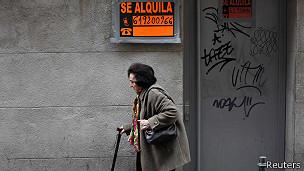 Mujer camina frente a una tienda cerrada a raiz de la crisis