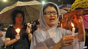 香港维多利亚公园六四烛光悼念晚会上一名穿上雨衣的女士高举烛光(4/6/2013)