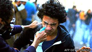 Manifestante tenta lavar olhos de outro no Egito, em 2011, contra efeitos do gás | Foto: AFP
