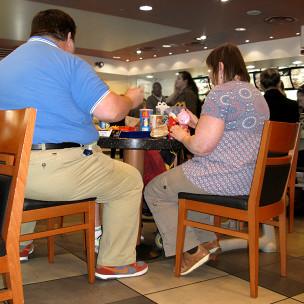 Personas comiendo en restaurante de comida rápida