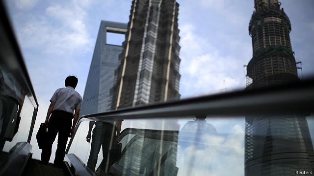 Una persona en las escaleras mecánicas en el distrito financiero de Shangai