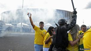 Aficionados del fútbol atraviesan el lugar en que se enfrentan policía y manifestantes junto al estadio de Garrincha, en Brasilia.