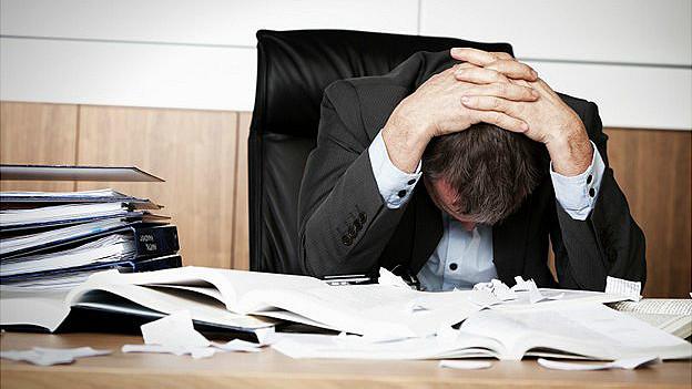 hombre se lleva las manos a la cabeza en un su escritorio