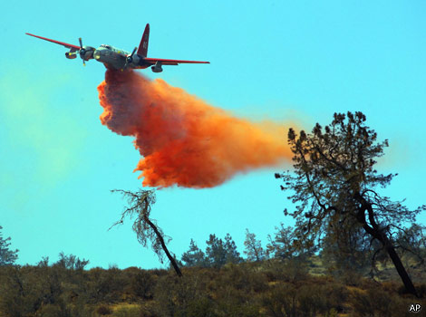 A plane drops water to put out a fire