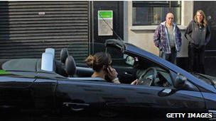 Mujer maneja carro con celular