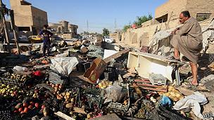 hombre observa edstrozos tras atentado en una mercado de Bagdad