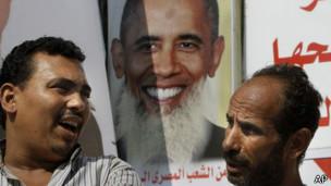 dois egípcios diante de cartaz de Obama   Foto: AP