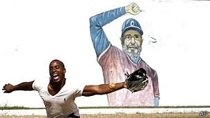 Hombre jugando béisbol frente a una imagen de Fidel Castro