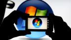 Un hombre toma una foto del logo de Microsoft con un teléfono Nokia