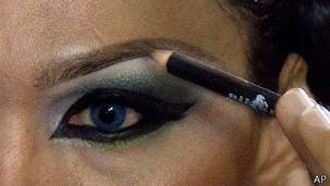 Una mujer pinta sus cejas.