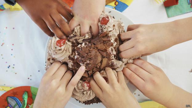Manos de chicos en pastel de cumpleaños