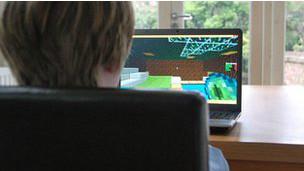 Niño viendo a una computadora