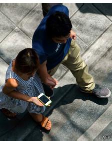 Persona camina mientras ve su teléfono inteligente.
