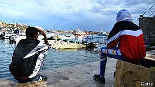 Выжившие мигранты на берегу Лампедузы