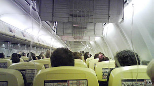 Una cabina de avión con las máscaras de oxígeno afuera