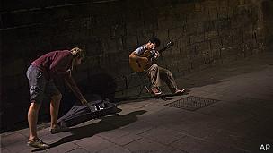 Álvaro Concha toca guitarra y vende discos en las calles de Barcelona