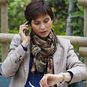 Mujer en el telefono mirando el reloj