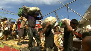 Moradores saqueiam escombros de supermercado destruído pelo tufão