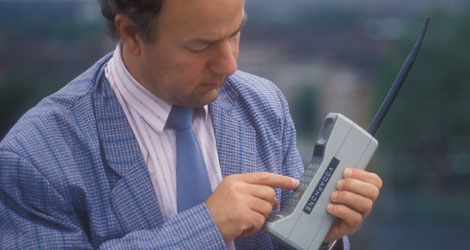 A man using an old mobile phone from the 1980s