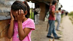 Una niña hondureña llora mientras su casa es desmantelada en un barrio de invasión.