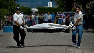 Funcionarios judiciales cargan un cadáver.
