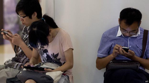 Chineses com seus tablets e smartphones em Pequim, em foto de arquivo (AP)