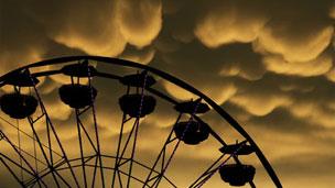 Колесо обозрения на фоне облаков