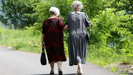 Две пожилые женщины идут по парку