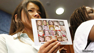 Una mujer muestra la imagen de los niños que murieron en Newtown