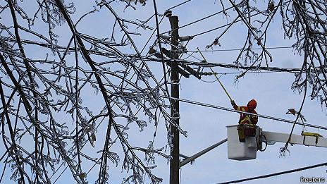 Un trabajador trata de quitarle el hielo a un cable