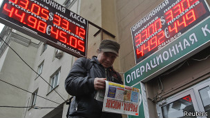 Москвич читает газету на фоне пункта обмена валюты