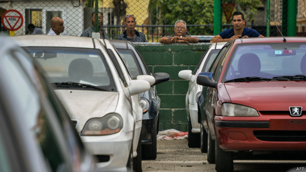 Cubanos en La Habana miran coches nuevos y usados en un concesionario
