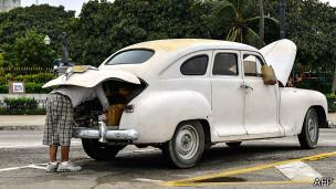Hombre intenta reparar su viejo coche en La Habana