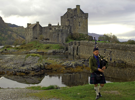 A piper plays his bagpipes outside Eilean Donan Castle in Scotland