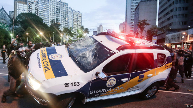 Manifestantes do 'Não Vai Ter Copa' viram carro da polícia. Foto: AFP