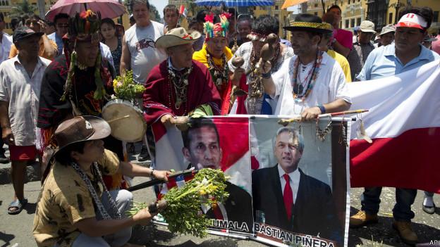 Cerimônia em Lima (com as fotos dos presidentes do Peru e do Chile) após decisão em Haia (AP)