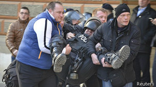 Personas ayudan a un policía herido