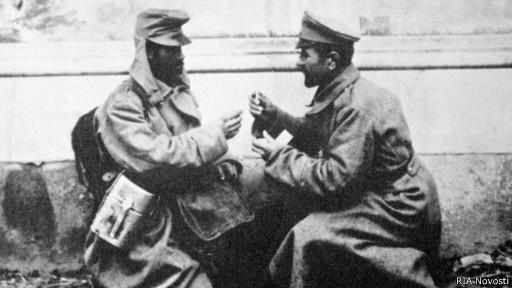 Австрийский (слева) и русский (справа) солдаты обмениваются папиросами во время Первой мировой войны.
