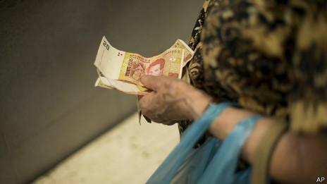 Mano sostiene billtes de 20 pesos