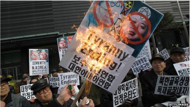 Coreanos quemando carteles con la imagen de Kim Jong Un