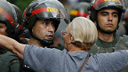 Mujer encara a un policía en las protestas de Venezuela