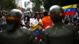 Policías frente a manifestantes opositores en Venezuela