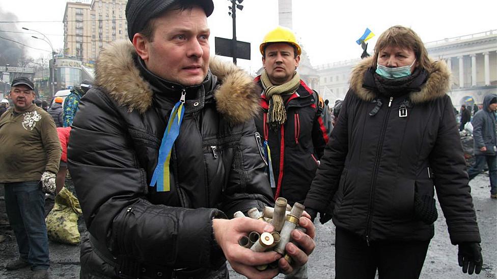 Демонстрант, показывающий  гильзы
