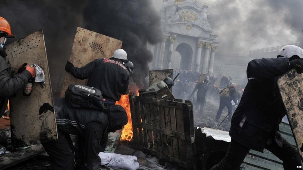 Протестующие укрываются за щитами