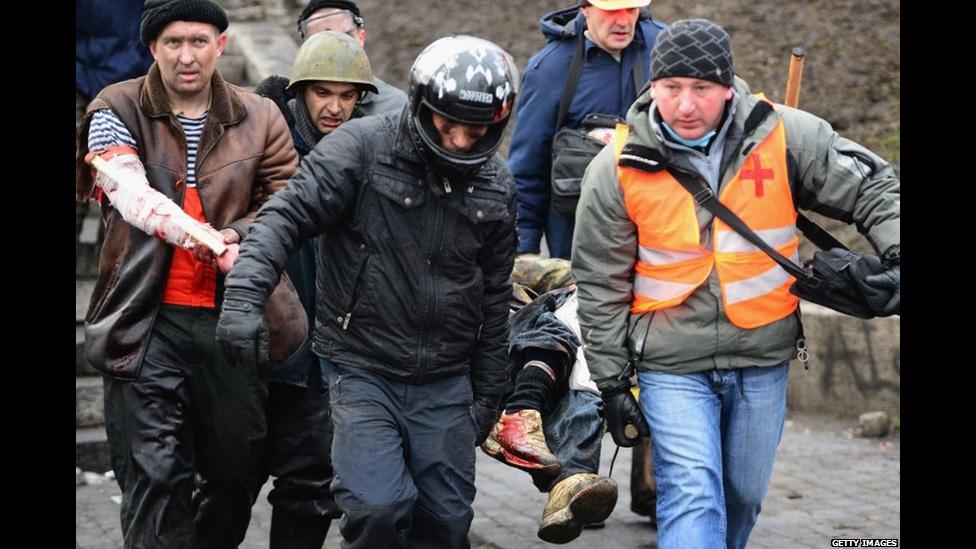 Врачи и добровольцы выносят раненого