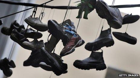 Pares de zapatos cuelgan de los cables de electricidad entre dos edificios en una callejuela de Melbourne.
