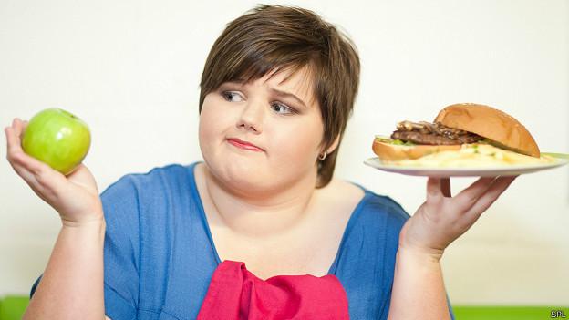 Chica decidiendo entre manzana y hamburguesa
