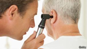 Un doctor examina el oido de un paciente.