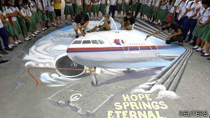 Jóvenes escriben mensajes de buena voluntad junto al dibujo de un avión en el suelo