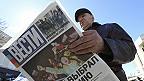 """Hombre en Crimea lee periódico con titular """"Crimea elige a Rusia"""""""